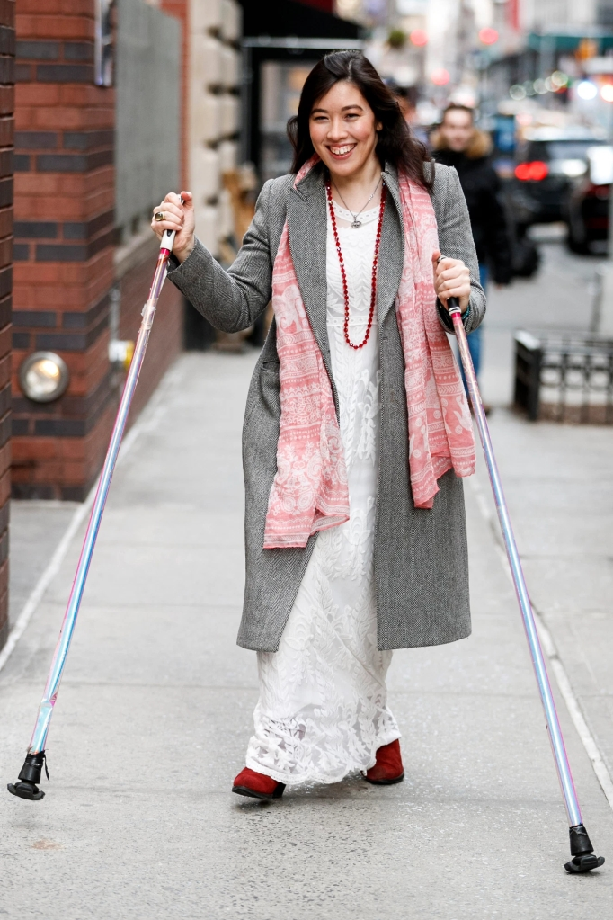 Xian smiling in motion on a NYC street in a white lace dress full grey coat Photo for NY Post by Anne Wermiel
