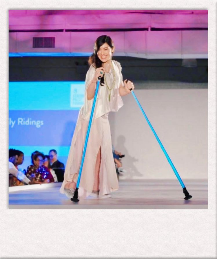 Xian Horn on the CP Foundation Design for Disability runway wearing a custom-made silk top and skirt, holding ski poles, smiling at the camera.