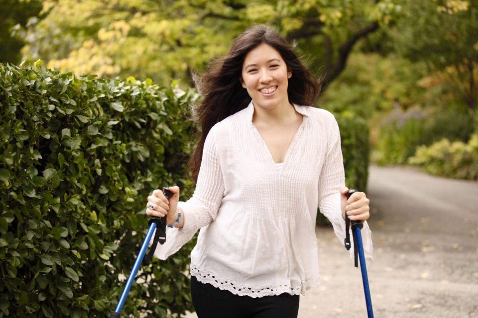 Xian smiling at the camera standing in a white blouse with her ski poles.