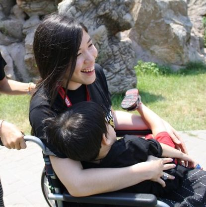Side pic of Xian smiling sitting in wheelchair and holding a child on her lap