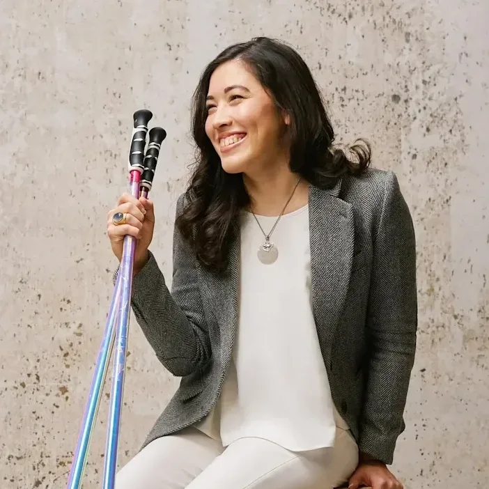 Xian smiling in a white jumpsuit and grey herringbone blazer holding her ski poles and sitting on an apple cart