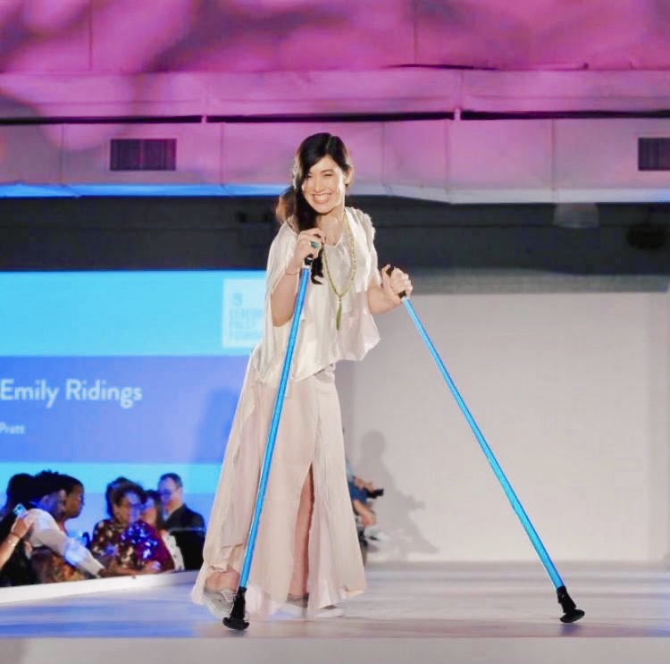 Xian turned toward the camera smiling standing on the runway in a sustainable silk top and tencel skirt, holding her iridescent ski poles.